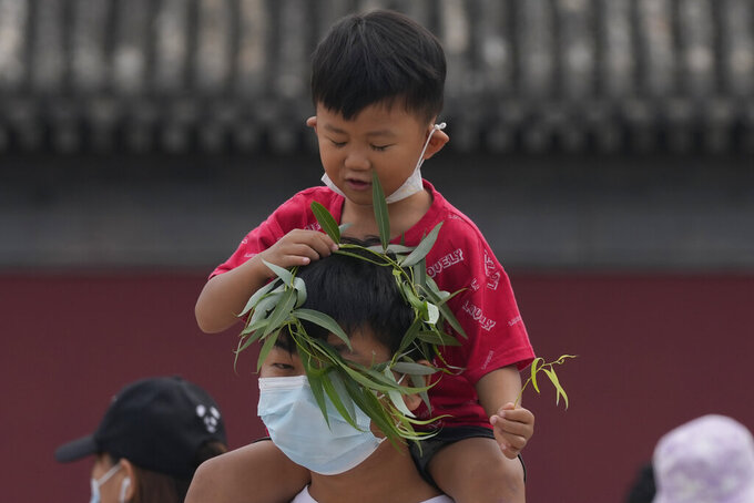 A child puts a wreath over the head of a man wearing a mask in Beijing Tuesday, Aug. 3, 2021. The coronavirus's delta variant is challenging China's costly strategy of isolating cities, prompting warnings that Chinese leaders who were confident they could keep the virus out of the country need a less disruptive approach. (AP Photo/Ng Han Guan)