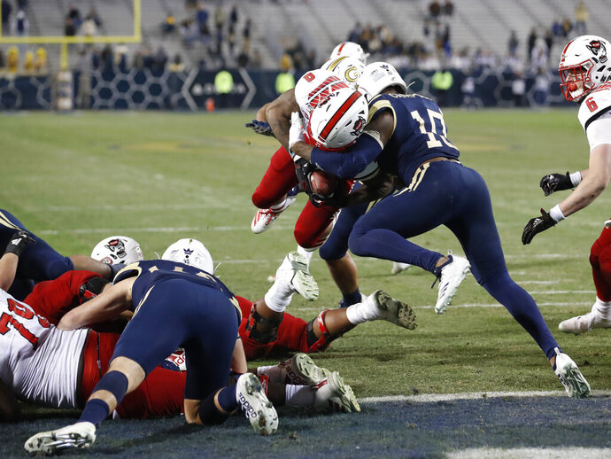 North Carolina State running back Ricky Person Jr. (8) dives in for a touchdown as Georgia Tech defensive back Christian Campbell (10) defends during the second half of an NCAA college football game Thursday, Nov. 21, 2019, in Atlanta. Georgia Tech won 28-26. (AP Photo/John Bazemore)