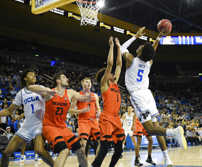 UCLA guard Chris Smith, right, attempts the go-ahead shot while Oregon State guard Stephen Thompson Jr., second from right, defends during the second half of an NCAA college basketball game as center Moses Brown, left, and center Gligorije Rakocevic work for position under the basket in Los Angeles, Thursday, Feb. 21, 2019. UCLA won 68-67. (AP Photo/Kelvin Kuo)
