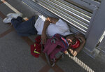A migrant sleeps on the ground after camping out on the Gateway International Bridge that connects downtown Matamoros, Mexico with Brownsville, Thursday, Oct. 10, 2019. Migrants wanting to request asylum camped out on the international bridge leading from Mexico into Brownsville, Texas, causing a closure of the span. (AP Photo/Fernando Llano)