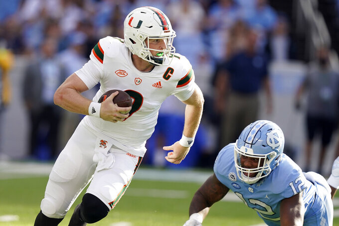 Miami quarterback Tyler Van Dyke (9) scrambles against North Carolina linebacker Tomon Fox (12) during the first half of an NCAA college football game in Chapel Hill, N.C., Saturday, Oct. 16, 2021. (AP Photo/Gerry Broome)