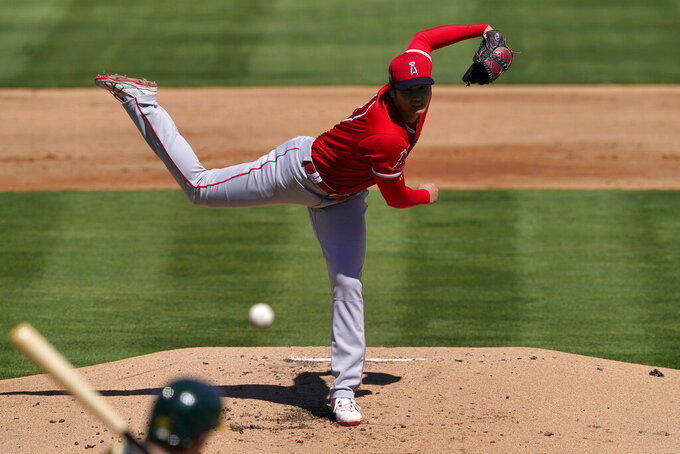 Los Angeles Angels pitcher Shohei Ohtani (17) throws against the Oakland Athletics during the first inning of a spring training baseball game, Friday, March 5, 2021, in Mesa, Ariz. (AP Photo/Matt York)