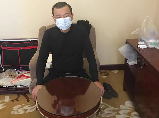 In this photo taken on Feb. 19, 2020 and released by Chen Chi-chuan, Chen Chi-chuan, 51, a Taiwanese electrical and plumbing contractor poses for a photo in his room at the Vienna International Hotel where he's lived in since Jan. 28 in Shiyan city in central China's Hubei province. Chen and about 1,000 other Taiwanese citizens are stuck behind doors in locked-down Chinese cities because their government cannot agree with China on how to arrange charter flights. Some are losing business income, risking too many absences from work and wondering how their children, if also stranded, will make up lost school days. (Chen Chi-chuan via AP)