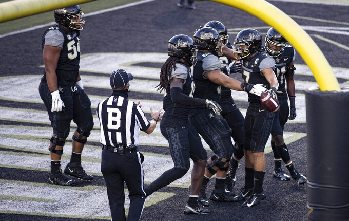 Vanderbilt wide receiver Cam Johnson (7) celebrates a touchdown with teammates during the first half of an NCAA college football game against Tennessee, Saturday, Dec. 12, 2020, in Nashville, Tenn. (AP Photo/Wade Payne)