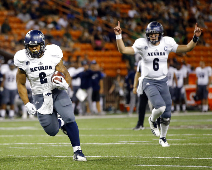 Nevada quarterback Kaymen Cureton (8) reacts as Nevada running back Devonte Lee (2) attempts to make a touchdown against Hawaii during the second quarter of an NCAA college football game, Saturday, Oct. 20, 2018, in Honolulu. (AP Photo/Marco Garcia)