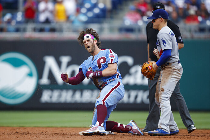 Philadelphia Phillies' Bryce Harper, left, celebrates past Los Angeles Dodgers shortstop Enrique Hernandez after hitting an RBI-single during the eighth inning of a baseball game, Thursday, July 18, 2019, in Philadelphia. Philadelphia won 7-6. (AP Photo/Matt Slocum)