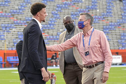 Arkansas quarterback Feleipe Franks, left, talks with Florida athletic director Scott Stricklin on the field before an NCAA college football game, Saturday, Nov. 14, 2020, in Gainesville, Fla. (AP Photo/Phelan M. Ebenhack)