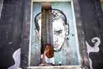 A woman looks from a window amid the new coronavirus pandemic at Morro da Providencia favela, Rio de Janeiro, Brazil, Thursday, Sept. 3, 2020. Rio de Janeiro is deploying a program to administer 20 thousand COVID-19 quick tests in the city's poor neighborhoods to track the progress of the disease. (AP Photo/Silvia Izquierdo)