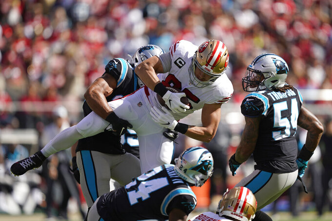 San Francisco 49ers tight end George Kittle is stopped with the ball by Carolina Panthers strong safety Eric Reidas as Panthers cornerback James Bradberry (24) and outside linebacker Shaq Thompson (54) look on during the first half of an NFL football game in Santa Clara, Calif., Sunday, Oct. 27, 2019. (AP Photo/Tony Avelar)