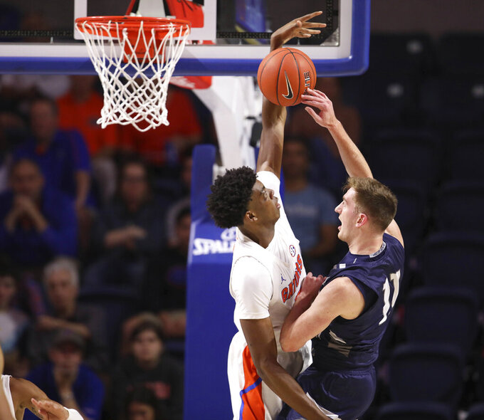 Florida forward Omar Payne (5) blocks the shot of North Florida guard Garrett Sams (11) during the first half of an NCAA college basketball game Tuesday, Nov. 5, 2019, in Gainesville, Fla. (AP Photo/Matt Stamey)