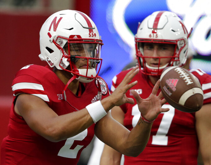 FILE- In this Sept. 1, 2018, file photo, Nebraska quarterback Andrew Bunch (17) watches as quarterback Adrian Martinez (2) catches the ball before an NCAA college football game against Akron in Lincoln, Neb. The circumstances for Nebraska are far from ideal as it nears its first road game under new coach Scott Frost next week at Michigan. The Cornhuskers went late into this week not knowing the health status of true freshman quarterback Adrian Martinez, making their Saturday game against Troy a little trickier. If Martinez cannot play, sophomore walk-on Andrew Bunch will make his first start. (AP Photo/Nati Harnik)