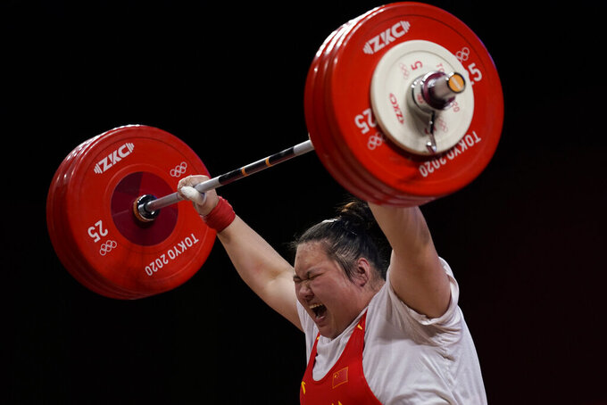 Li Wenwen of China shouts as she completes her final lift to win gold in the women's +87kg weightlifting event at the 2020 Summer Olympics, Monday, Aug. 2, 2021, in Tokyo, Japan. (AP Photo/Seth Wenig)