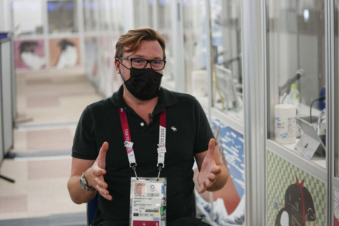 Alexandre Ponomarev, the chief interpreter for the Tokyo Games, gestures during an interview with The Associated Press at the main press center during the 2020 Summer Olympics, Friday, July 30, 2021, in Tokyo, Japan. Ponomarev worked his first Olympics in 2008 in Beijing, and took over as the chief in Rio de Janeiro in 2016. He said his mother got him started with language-learning, smuggling DVDs of American films into the old Soviet Union. One by one, the languages piled up.(AP Photo/Luca Bruno)