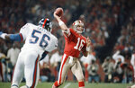 File-This Dec. 1, 1986, file photo shows  San Francisco 49ers quarterback Joe Montana (16), passing before New York Giants linebacker Lawrence Taylor (56), can reach him during the first quarter of their NFL game in Candlestick Park, San Francisco. Members of a special panel of 26 selected all of them for the position as part of the NFL's celebration of its 100th season. All won league titles except Marino. All are in the Hall of Fame except Brady and Manning, who are not yet eligible.  On Friday, Dec. 27, 2019, quarterback was the final position revealed for the All-Time Team.  (AP Photo/Paul Sakuma, File)