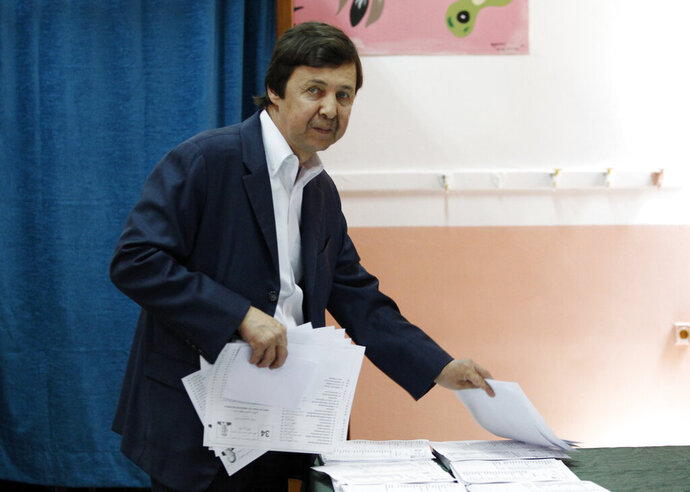 FILE - In this Thursday, May 4, 2017 file photo, Said Bouteflika, the brother of Algerian President Abdelaziz Bouteflika, takes ballots before voting in Algiers. A military tribunal has opened the high-profile trial of Said Bouteflika and two ex-intelligence chiefs, one whose name alone once made Algerians tremble. (AP Photo/Sidali Djarboub, File)