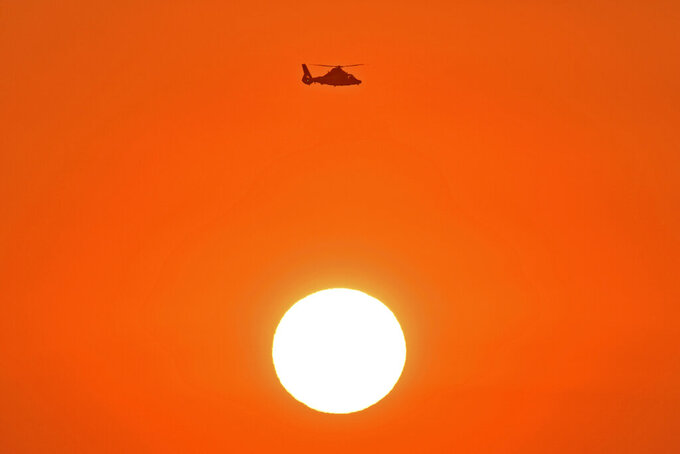A Coast Guard helicopter flies above the setting sun while patrolling the waters near the Golden Gate Bridge, viewed from Treasure Island Wednesday, Sept. 2, 2020, in San Francisco. Triple-digit temperatures are likely over a vast stretch of the state, and even coastal areas could see higher temperatures, forecasters said. (Jose Carlos Fajardo/Bay Area News Group via AP)