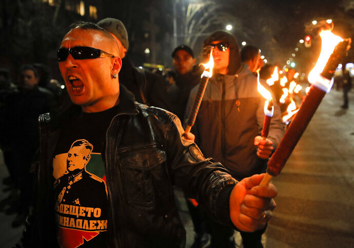 A man holds a flare chanting the name of Gen. Hristo Lukov, who had supported Germany during the Second World War, depicted on his t-shirt, as people take part in the