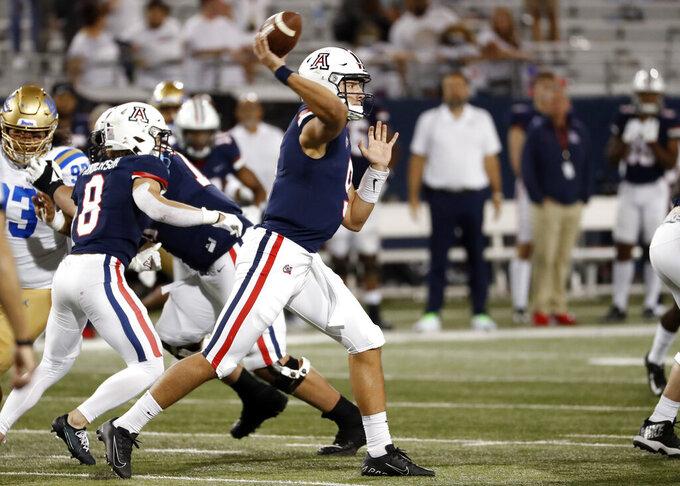 Arizona quarterback Gunner Cruz (9) throws during the second half of an NCAA college football game against UCLA Saturday, Oct. 9, 2021, in Tucson, Ariz. (AP Photo/Chris Coduto)