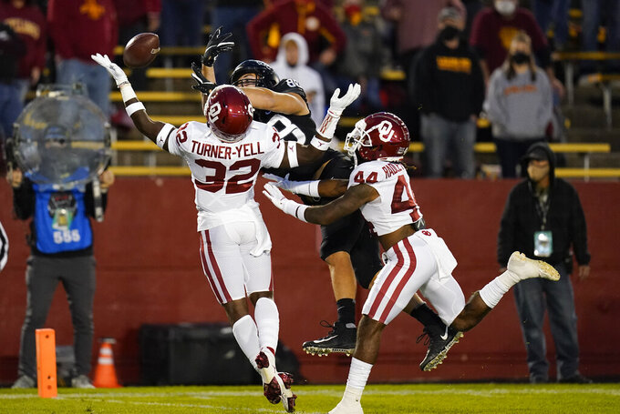 Oklahoma defensive back Delarrin Turner-Yell (32) and defensive back Brendan Radley-Hiles, right, break up a pass intended for Iowa State tight end Charlie Kolar, center, during the first half an NCAA college football game, Saturday, Oct. 3, 2020, in Ames, Iowa. (AP Photo/Charlie Neibergall)