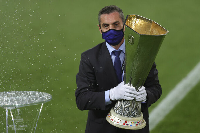 An UEFA official carries the trophy ahead of the Europa League final soccer match between Sevilla and Inter Milan in Cologne, Germany, Friday, Aug. 21, 2020. (Friedemann Vogel/Pool via AP)