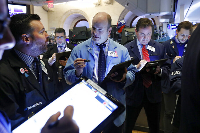 Frank Masiello, left, and Peter Mancuso, center, work with fellow traders on the floor of the New York Stock Exchange, Friday, Feb. 14, 2020. U.S. stocks wobbled between small gains and losses in early trading Friday as investors focused on another round of mostly solid corporate earnings. (AP Photo/Richard Drew)