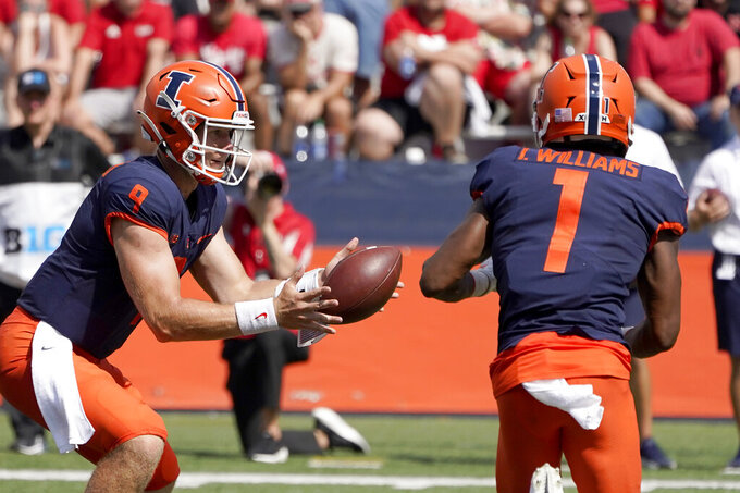 Illinois quarterback Artur Sitkowski tosses the ball to wide receiver Isaiah Williams in the backfield for a touchdown reception during the second half of an NCAA college football game against Nebraska Saturday, Aug. 28, 2021, in Champaign, Ill. Illinois won 30-22. (AP Photo/Charles Rex Arbogast)