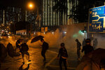 In this Oct. 6, 2019, photo, protestors face police tear gas in Hong Kong. Shouting