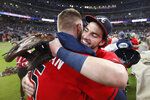 Atlanta Braves shortstop Dansby Swanson (7), right, embraces first baseman Freddie Freeman (5) after defeating the San Francisco Giants in a baseball game to clinch the NL East baseball title Friday, Sept. 20, 2019, in Atlanta. (AP Photo/John Bazemore)