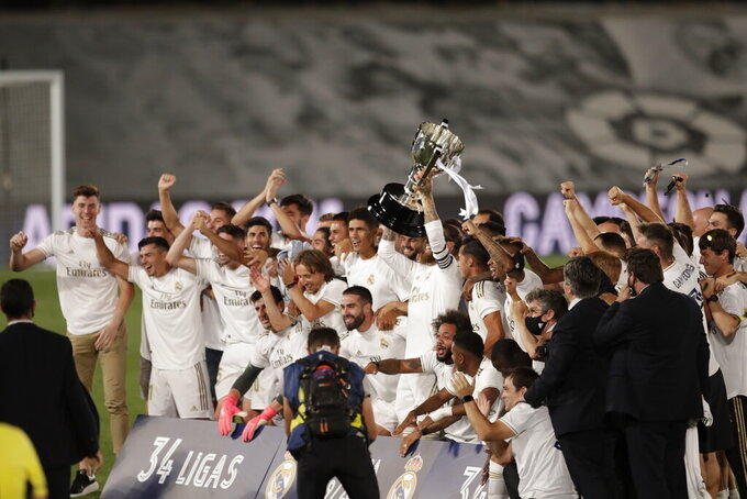 Real Madrid's lift the cup as they celebrate winning the Spanish La Liga 2019-2020 following a soccer match between Real Madrid and Villareal at the Alfredo di Stefano stadium in Madrid, Spain, Thursday, July 16, 2020. (AP Photo/Bernat Armangue)