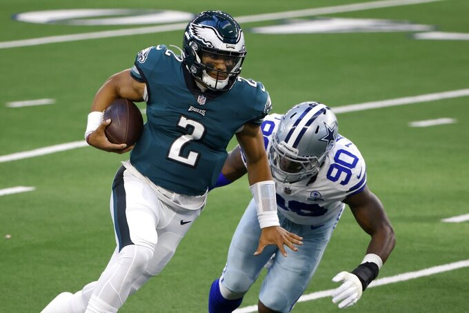 Philadelphia Eagles quarterback Jalen Hurts (2) escapes pressure from Dallas Cowboys defensive end DeMarcus Lawrence (90) in the first half of an NFL football game in Arlington, Texas, Sunday, Dec. 27. 2020. (AP Photo/Ron Jenkins)