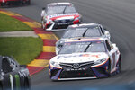 Denny Hamlin (11) leads Tyler Reddick (8) as they turn into the Esses during a NASCAR Cup Series auto race in Watkins Glen, N.Y., on Sunday, Aug. 8, 2021. (AP Photo/Joshua Bessex)
