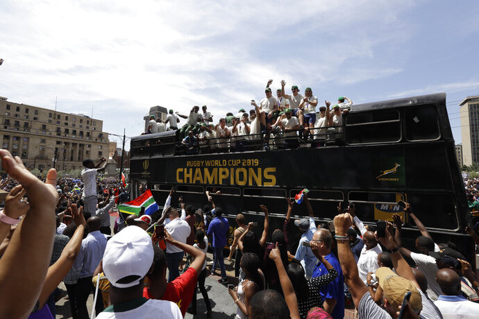 Rugby fans surround the bus of the South African Springbok rugby team, during a victory parade in Pretoria, South Africa, Thursday, Nov. 7, 2019. South Africa's Rugby World Cup-winning team have started a five-day victory tour where they will carry the trophy across the country. South Africa beat England in Saturday's final in Japan to clinch a third World Cup title.  (AP Photo/Themba Hadebe)
