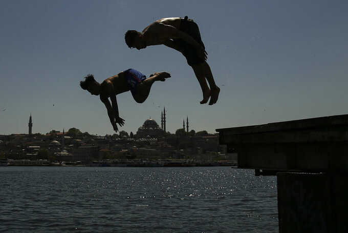 Backdropped by the historical Suleymaniye mosque youths jump from the Galata Bridge into the Golden Horn leading to the Bosphorus Strait separating Europe and Asia, in Istanbul, Friday, May 14, 2021. Turkey is in the final days of a full coronavirus lockdown and the government has ordered people to stay home and businesses to close amid a huge surge in new daily infections. But millions of workers are exempt and so are foreign tourists. Turkey is courting international tourists during an economic downturn and needs the foreign currencies that tourism brings to help the economy as the Turkish lira continues to sink. (AP Photo/Emrah Gurel)