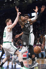 Boston Celtics forward Gordon Hayward (20) and center Robert Williams III, right, guard Brooklyn Nets guard D'Angelo Russell (1) during the first half of an NBA basketball game, Saturday, March 30, 2019, in New York. (AP Photo/Mary Altaffer)