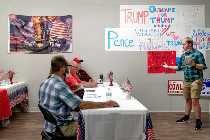Ryan Retza, right, Trump Victory regional field director, leads volunteers in a training event at a campaign office in Appleton, Wis., Aug. 20, 2020. Republicans here say that President Donald Trump propelled the country to new heights with tax and regulatory cuts, only to be brought low by the force majeure of a virus, and that most voters will hold him blameless. (AP Photo/David Goldman)