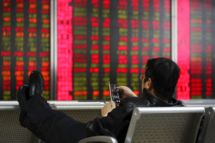 A man checks stock prices through his smartphone at a brokerage house in Beijing, Friday, Dec. 6, 2019. Shares swung higher in Asia on Friday after a wobbly day of trading on Wall Street as investors awaited a U.S. government jobs report and kept an eye out for developments in China-U.S. trade talks. (AP Photo/Andy Wong)
