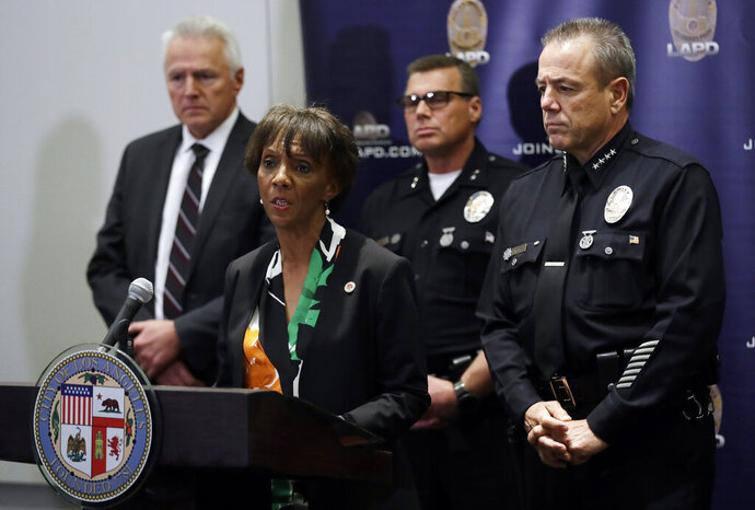 Los Angeles County District Attorney Jackie Lacey, second from left, addresses the media regarding the arrest of Dr. George Tyndall, Wednesday, June 26, 2019, in Los Angeles. Tyndall was charged today with sexually assaulting multiple women at the student health center while he worked as a gynecologist at the University of Southern California, the Los Angeles County District Attorney's Office announced. (AP Photo/Marcio Jose Sanchez)