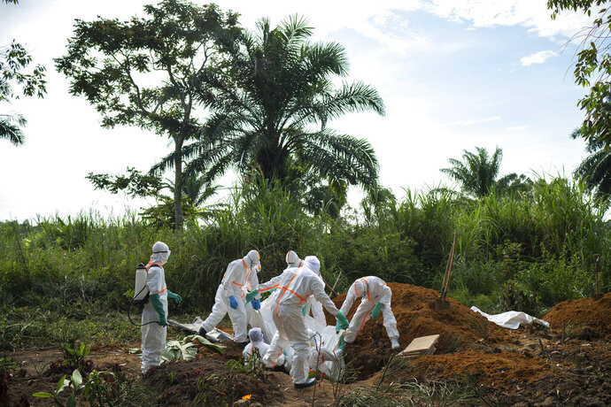 In this Sunday, July 14, 2019 photo, workers bury the remains of Mussa Kathembo, an Islamic scholar who had prayed over those who were sick in Beni, Congo. Kathembo died of Ebola. (AP Photo/Jerome Delay)