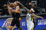 Phoenix Suns guard Devin Booker (1) has the ball knocked away by Utah Jazz guard Jordan Clarkson (00) during the second half of an NBA basketball game, Wednesday, April 7, 2021, in Phoenix. (AP Photo/Matt York)