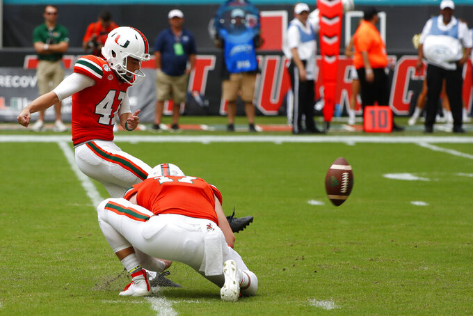 Miami kicker Turner Davidson (47) attempts a field goal as punter Jack Spicer (17) holds during the second half of an NCAA college football game against Georgia Tech, Saturday, Oct. 19, 2019, in Miami Gardens, Fla. Georgia Tech's Antwan Owens blocked the Miami chip-shot field goal in the final seconds of regulation and went on to win 28-21 in overtime. (AP Photo/Wilfredo Lee)