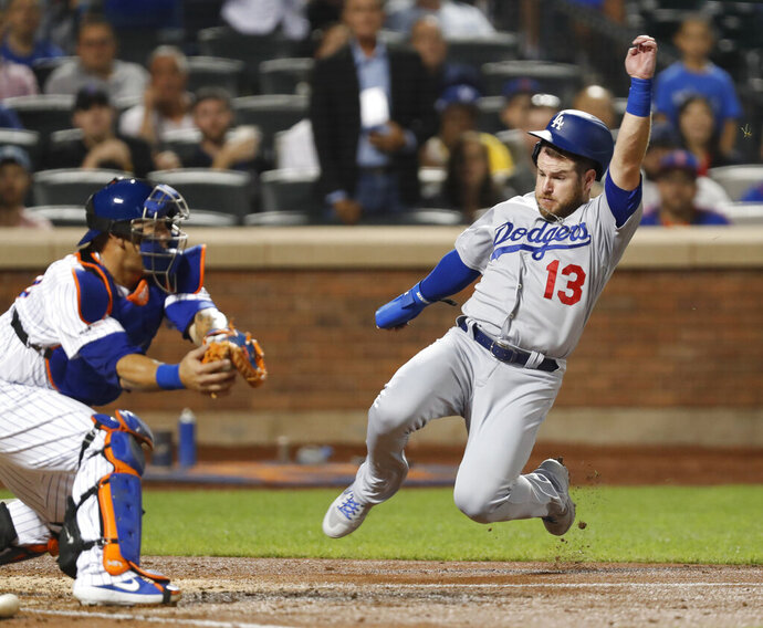 New York Mets catcher Wilson Ramos, left, has the ball in hi glove as Los Angeles Dodgers' Max Muncy (13) runs home to score on Cory Seager's fourth-inning RB-single in a baseball game Sunday, Sept. 15, 2019, in New York. (AP Photo/Kathy Willens)