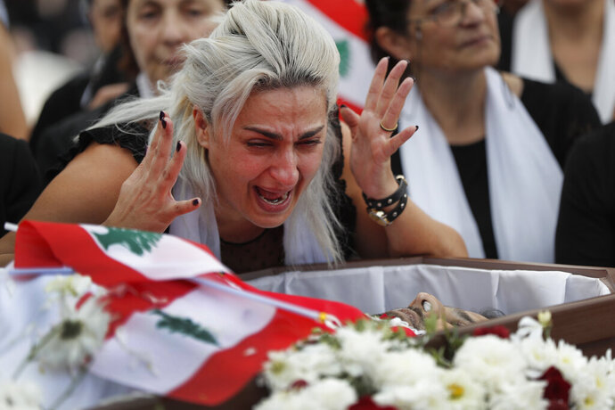 Lara, the wife of Alaa Abou Fakher who was killed by a Lebanese soldier on Tuesday night protests in southern Beirut, mourns over her husband's body during his funeral procession, in Choueifat neighborhood, Lebanon, Thursday, Nov. 14, 2019. For nearly a month, the popular protests engulfing Lebanon have been startlingly peaceful. But the death of Fakher, a 38-year-old father, by a soldier, the first such fatality in the unrest, points to the dangerous, dark turn the country could be heading into. (AP Photo/Hussein Malla)