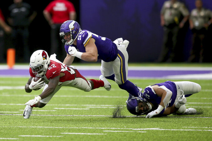Arizona Cardinals running back T.J. Logan (22) runs from Minnesota Vikings linebacker Cameron Smith (59) during the second half of an NFL preseason football game, Saturday, Aug. 24, 2019, in Minneapolis. (AP Photo/Jim Mone)