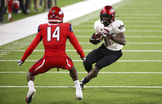 UNLV running back Charles Williams tries to avoid Fresno State defensive back Jaran Bryant during the second half of an NCAA college football game in Fresno, Calif., Friday, Oct. 18, 2019. (AP Photo/Gary Kazanjian)