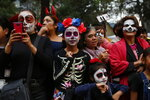 People attend the Catrinas parade down Mexico City's iconic Reforma avenue during celebrations for the Day of the Dead in Mexico, Saturday, Oct. 26, 2019. (AP Photo/Ginnette Riquelme)