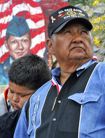 FILE - In this March 23, 2005, file photo, a portrait of U.S. Army Spc. Lori Piestewa, is shown behind her father, Terry Piestewa, right, and her son, Brandon Piestewa, at a sunrise ceremony in Phoenix. Lori Piestewa, a member of the Hopi Tribe and a single mother of two, is believed to be the first American Indian woman killed while fighting for the U.S. military.