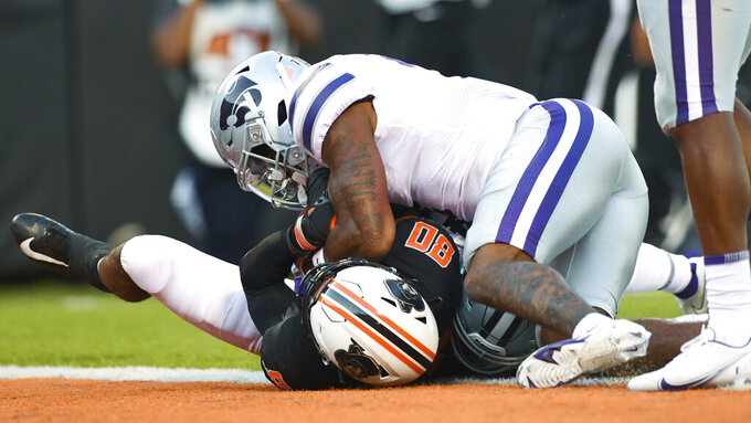 Oklahoma State wide receiver Brennan Presley (80) rolls into the end zone while being tackled by Kansas State defensive back TJ Smith (7) during an NCAA college football game Saturday, Sept. 25, 2021, in Stillwater, Okla.  (AP Photo/Brody Schmidt)