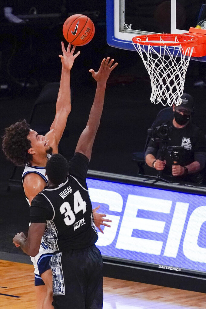 Villanova forward Jeremiah Robinson-Earl goes to the basket against Georgetown center Qudus Wahab (34) during the first half of an NCAA college basketball game in the quarterfinals of the Big East conference tournament, Thursday, March 11, 2021, in New York. (AP Photo/Mary Altaffer)