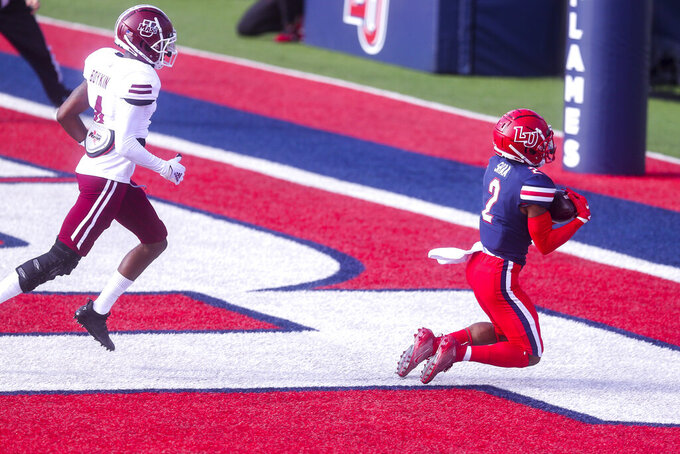 Liberty wide receiver Kevin Shaa (2) hauls in a touchdown as he is defended by Massachusetts player Noah Boykin (4) during the first half of a NCAA college football game on Friday, Nov. 27, 2020, at Williams Stadium in Lynchburg, Va. (AP Photo/Shaban Athuman)