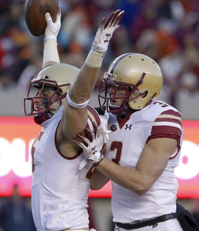 Korab Idrizi (85) and Michael Walker (3) of Boston College celebrate scoring on 22 yard touchdown play in the second half of an NCAA college football  game in Blacksburg Va., Saturday, Nov. 3 2018. Boston College won the game 31-21. (Matt Gentry/The Roanoke Times via AP)
